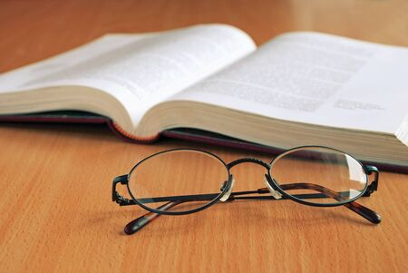 bibliomania: An open book and glasses on the table. Stock Photo