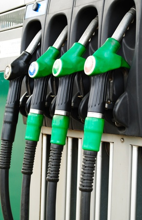 Gas station with three green handles and a black photo