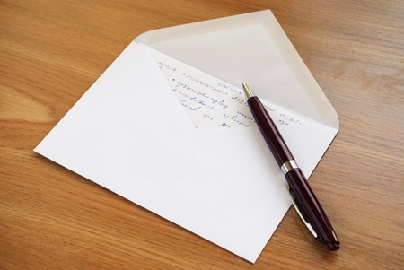 Mailing envelope and a pen on the table photo