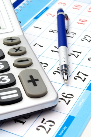 calendar, a calculator and a pen close-up photo