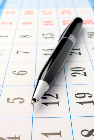 calendar and a pen are shown in close-up photo
