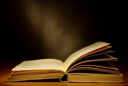 libros viejos: viejo libro sobre un fondo oscuro y haz de luz