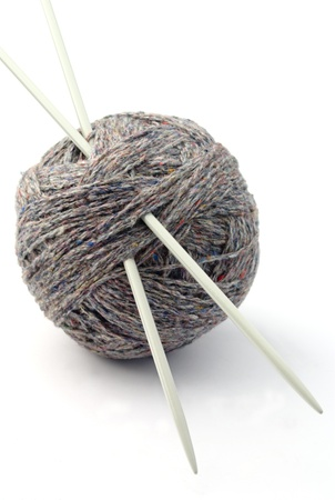ball of thread and needles for knitting on a white background photo