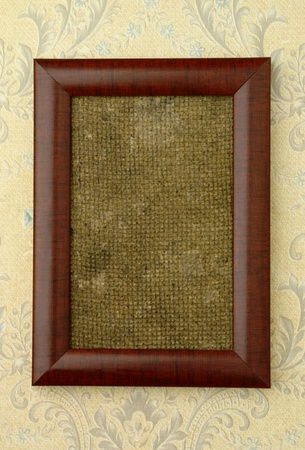 The brown frame on the wall with the old wallpaper. photo