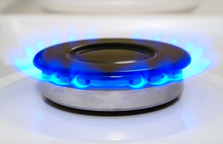 gas stove: gas burner with a flame burning home plate Stock Photo
