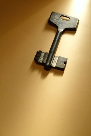 the old key on yellow paper illuminated by a beam of light photo