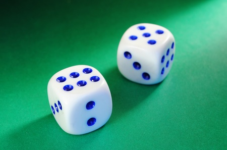 White dice with a blue dot illumination beam of light