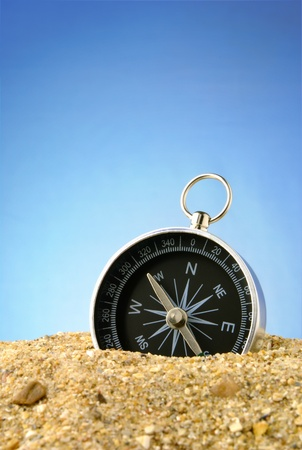 Compass on sea sand and a dark blue background Stock Photo - 11716041