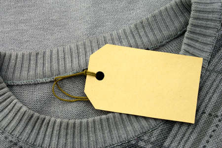 The label is attached to a sweater of gray color photo