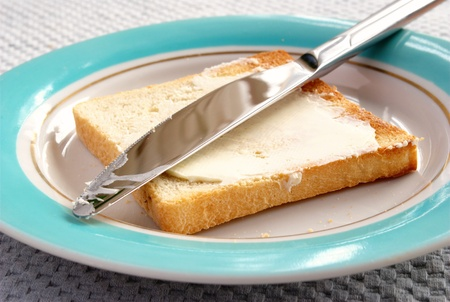 bread knife: toasted bread and butter in a bowl on the table