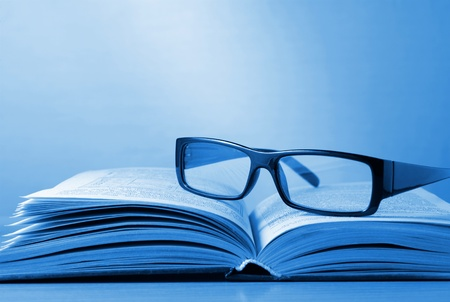 black-rimmed glasses and a book on the table photo