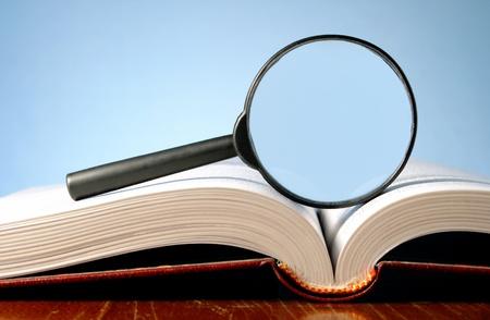 vergrootglas en een open boek op een tafel Stockfoto