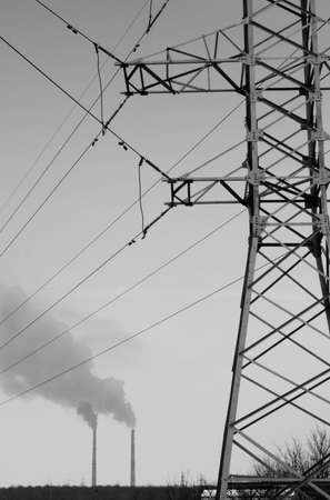 power line tower: electric pole, and the smoke of two pipes in the background