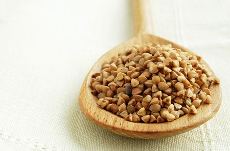 groat: buckwheat groats in a brown wooden spoon on a napkin