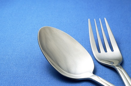 fork and spoon on blue napkin on the table Stock Photo