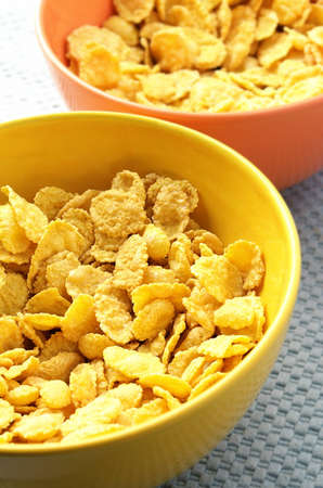 cornflakes: yellow and orange bowls with corn flakes Stock Photo