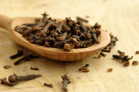 kitchen spice cloves in a wooden spoon on the board Stock Photo