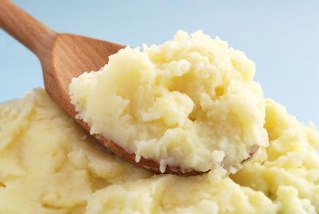 pure de papa: el puré de papas en una cuchara de madera marrón