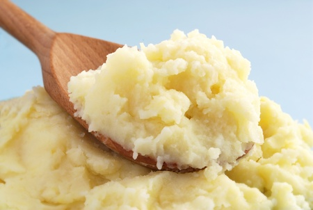 mashed potatoes: mashed potatoes in a brown wooden spoon