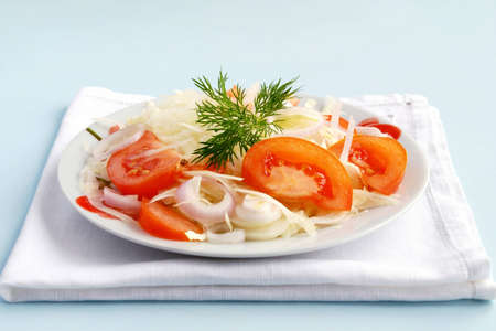 salad of tomato, cabbage and onions garnished with greenery photo