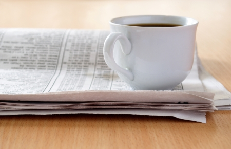 cup of coffee and the newspaper on the table photo