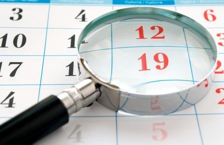 researches: lente di ingrandimento e un calendario per trovare il momento giusto Archivio Fotografico