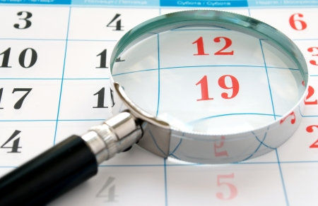 magnifying glass and a calendar to find the right time