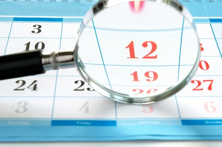 event organizer: magnifying glass and a calendar to find the right time