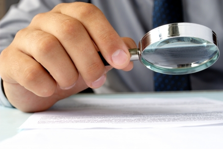 writing on glass: Businessman looking through a magnifying glass to documents