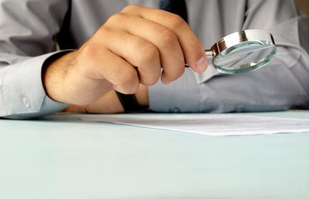 De negocios que mira a través de una lupa a los documentos