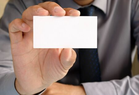 Businessman in office shows the business card in his hand photo