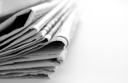 articles: newspaper with news closeup on white background Stock Photo