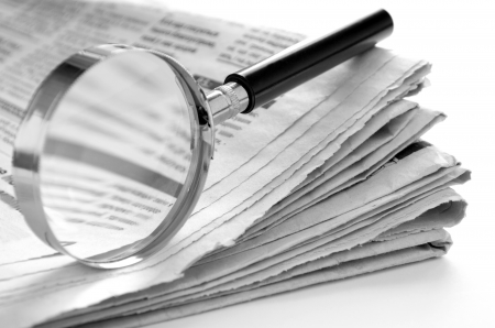 reading news: daily newspaper and a magnifying glass to find news