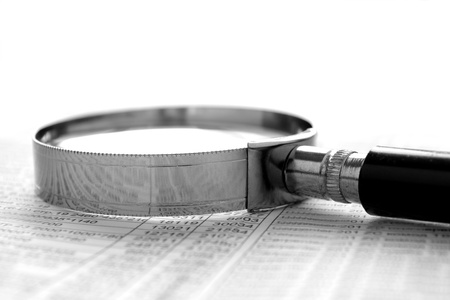 lupa: graf a zvětšovací sklo na stole, nástroje pro studium dokumentů Reklamní fotografie
