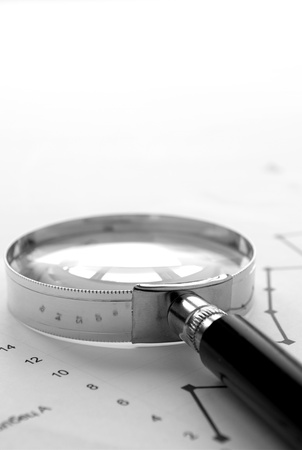 chart and a magnifying glass on the table, the tools for the study of documents photo