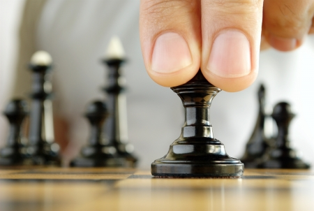 man playing chess, and shows the hand of chess pieces