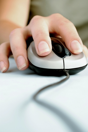 womans hand and computer mouse on the desk