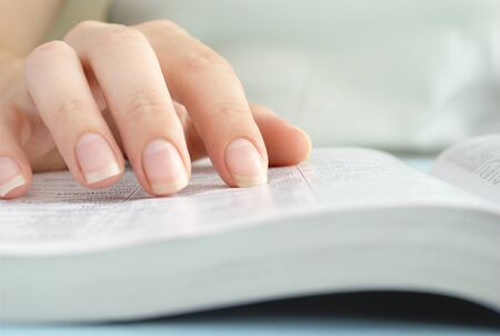data dictionary: girl reading a book, shows a close-up hand and a book