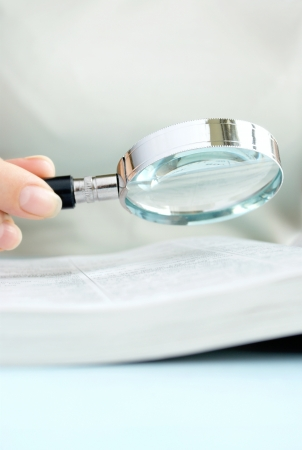 magnifying glass in hand, a young girl, and documents on the table photo