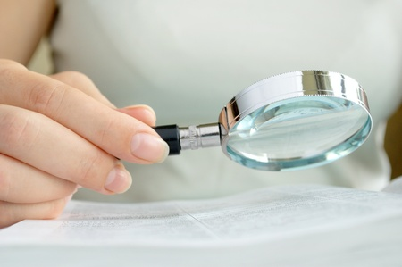 magnifying glass in hand, a young girl, and documents on the table Stock Photo