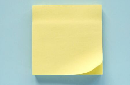 sticky notepaper: Yellow leaf of a reminder on a blue background Stock Photo