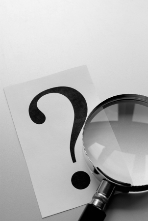 magnifying glass and a question mark on the paper photo