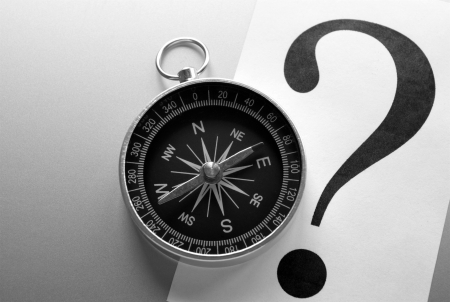 compass and question mark on a gray gradient background photo