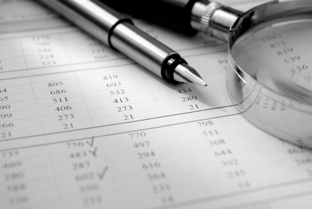 data sheet: pen, magnifying glass and the form of the figures on the table in the office Stock Photo