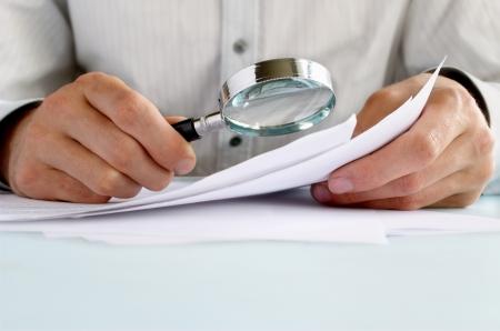 lupa: De negocios que mira a trav�s de una lupa a los documentos