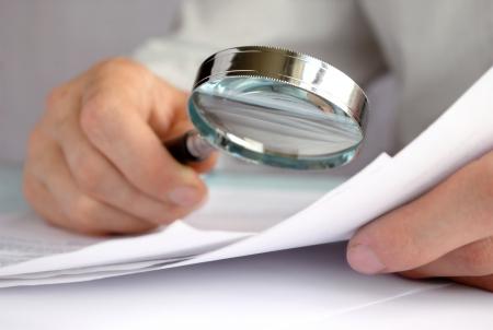 researches: Uomo d'affari guardando attraverso una lente di ingrandimento per documenti Archivio Fotografico