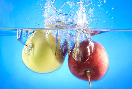 two ripe apples fell into the water, bubbles and splashes Stock Photo - 17163646