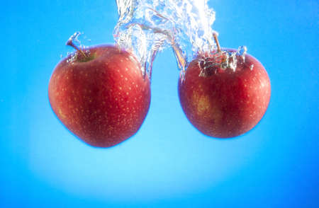 two ripe apples fell into the water, bubbles and splashes Stock Photo - 17163652