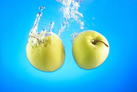 two ripe apples fell into the water, bubbles and splashes Stock Photo - 17163645