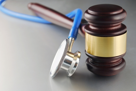 juridical: brown gavel and a medical stethoscope on gray background